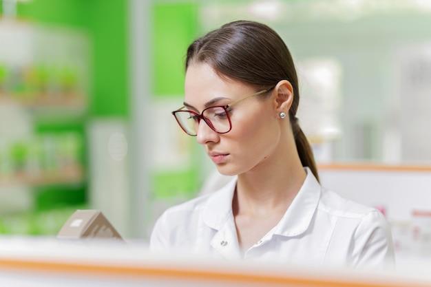 Eine hübsche, anmutige dunkelhaarige dame mit brille, gekleidet in einen weißen kittel, begutachtet sorgfältig die ware im regal in der apotheke. das profil des mädchens wird angezeigt. .
