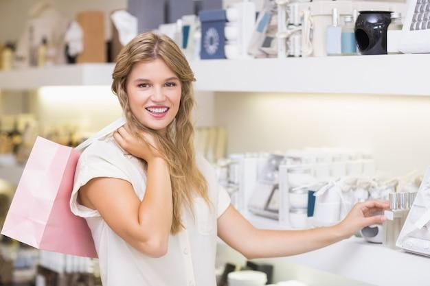 Eine hübsche blonde frau in einer parfümerie