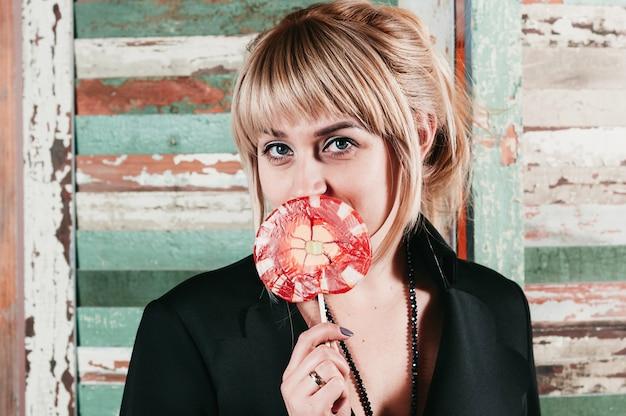Eine hübsche blondine im schwarzen kleid, die einen stock roter süßigkeit an ihrem mund hält