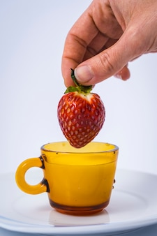 Eine hübsche erdbeere, die von einer frauenhand in eine tasse milch getaucht wird