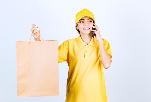Eine hübsche frau, die am telefon spricht und braune leere handwerkspapiertüte hält.
