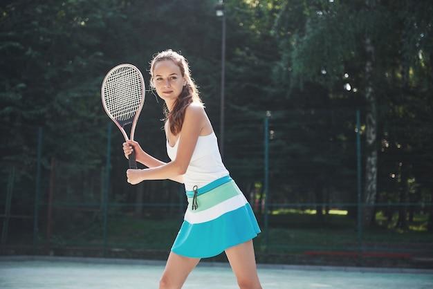 Eine hübsche frau, die einen sportbekleidungs-tennisplatz auf dem platz trägt.