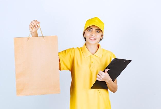 Eine hübsche frau in der gelben uniform, die braune leere handwerkspapiertüte hält.