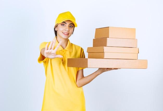 Eine hübsche frau in der gelben uniform, die braune leere kraftpapierkästen hält.