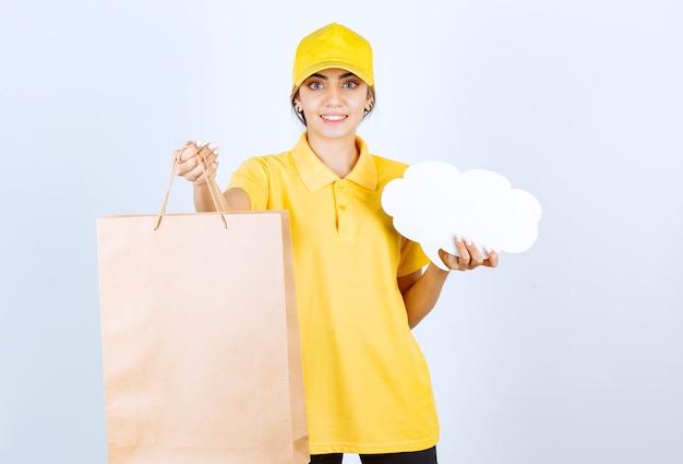 Eine hübsche frau in gelber uniform, die braune leere handwerkspapiertüte und leere sprechblase hält.