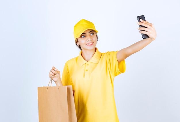 Eine hübsche frau in gelber uniform, die eine braune leere papiertüte hält und ein selfie macht.