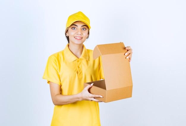 Eine hübsche frau in gelber uniform, die eine geöffnete braune leere kraftpapierschachtel hält.