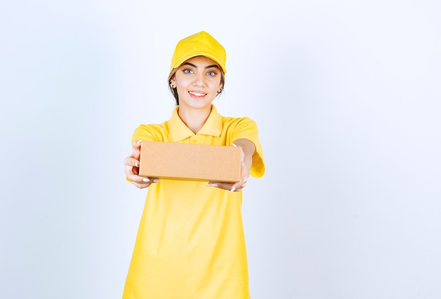 Eine hübsche frau in gelber uniform, die einen braunen leeren kraftpapierkasten hält.
