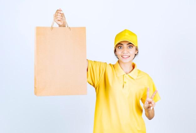 Eine hübsche frau in gelber uniform mit brauner leerer handwerkspapiertüte, die siegeszeichen zeigt.