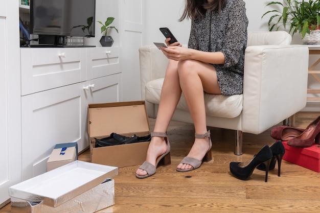 Eine hübsche frau in ihrem wohnzimmer wählt heute ein paar schuhe aus. sie kauft online mit ihrem smartphone ein und bezahlt die bestellung mit einer kreditkarte. online-web-shopping-konzept