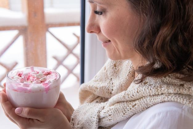 Eine hübsche frau trinkt am fenster einen drink mit marshmallows