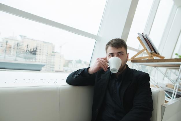 Eine hübsche geschäftsfrau, die in einem café am fenster sitzt und kaffee trinkt. kaffeepause im stilvollen modernen café
