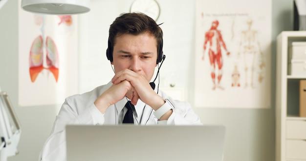 Eine hübsche junge ärztin mit headset vor ihrem laptop, die mit einem patienten spricht.