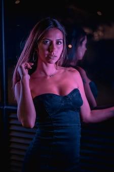 Eine hübsche junge brünette kaukasische frau in einem schwarzen kleid, das durch lila led-lichter beleuchtet wird und die kamera betrachtet. nachtstadtfotografie