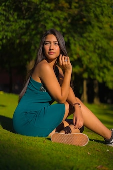 Eine hübsche junge brünette latina mit langen glatten haaren, die ein enges grünes kleid trägt. porträt eines mädchens, das auf dem gras in einem park mit bäumen im sommer sitzt