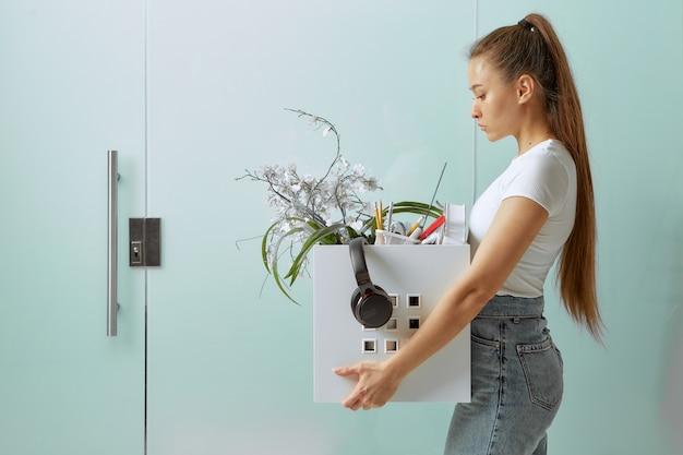 Eine hübsche junge frau geht mit büromaterial in einer kiste, traurig, nachdem sie wegen der krise bei der arbeit geschnitten und gefeuert wurde.