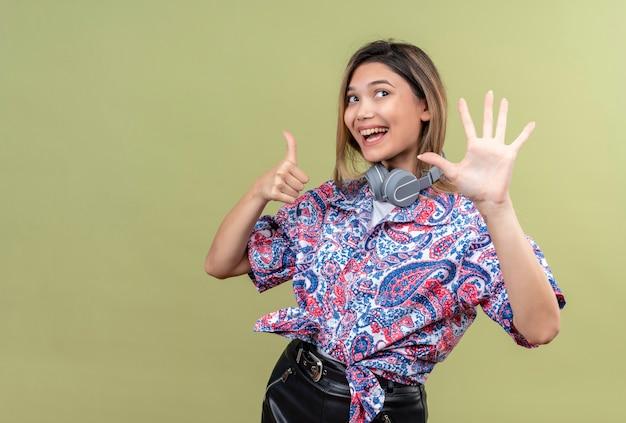 Eine hübsche junge frau im paisley-bedruckten hemd, die lächelnde kopfhörer trägt und nummer sechs auf einer grünen wand zeigt
