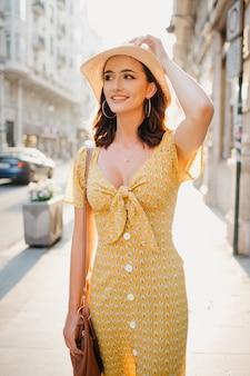 Eine hübsche junge frau in einem gelben kleid mit tiefem ausschnitt hält einen hut auf dem kopf auf dem sonnenuntergang in spanien.