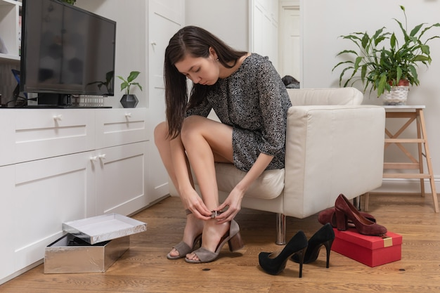 Eine hübsche junge frau in einem kurzen kleid sitzt auf einem stuhl im wohnzimmer neben dem kleiderschrank und wählt ein paar schuhe aus, die sie heute tragen möchte. ein mädchen probiert hochhackige schuhe an. konzept des online-web-shoppings