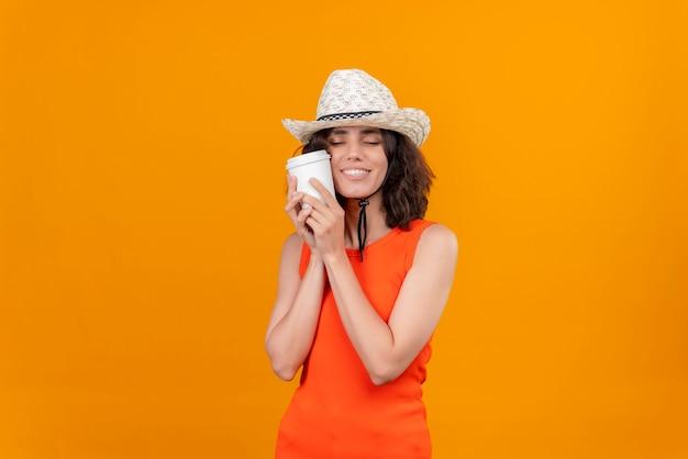 Eine hübsche junge frau mit kurzen haaren in einem orangefarbenen hemd, das sonnenhut trägt, der plastikbecher kaffee umarmt