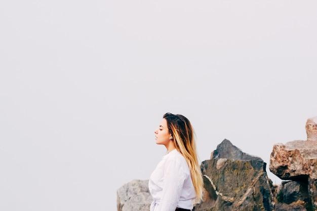 Eine hübsche junge langhaarige frau im weißen hemd am strand