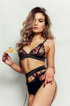 Eine hübsche junge sexy frau in schwarzer unterwäsche mit langen großen schnürsenkelhaaren, die leckeres großes stück pizza halten