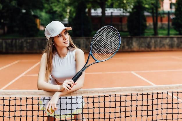 Eine hübsche, junge tennisspielerin, die ernsthaft auf dem platz steht.