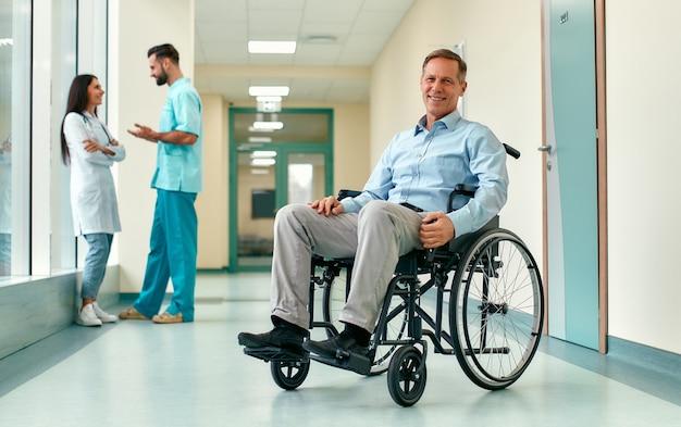 Eine hübsche lächelnde ältere behinderte person im rollstuhl sitzt mitten in einem klinikkorridor mit ärzten hinter ihm.