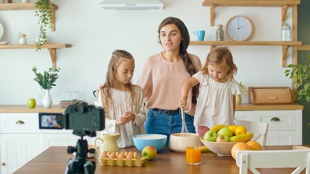 Eine hübsche mutter mit einer süßen tochter, die einen blog über das kochen dreht. video-blog über gesunde ernährung. mutter und tochter kochen gemeinsam vor der kamera. schöne mutter, die ihrer tochter das kochen beibringt.