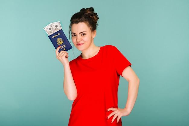 Eine hübsche reife frau, die einen pass mit gelddollar auf einem blauen hintergrundbild hält