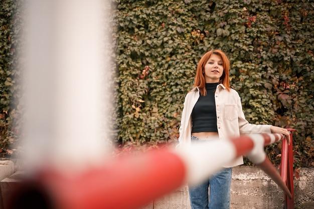 Eine hübsche rothaarige junge frau geht die straße entlang, sie trägt jeans und ein beigefarbenes hemd. schönes mädchen im lässigen stil mit einem lächeln im gesicht