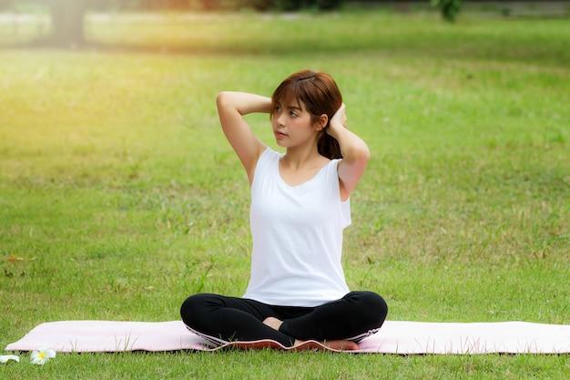 Eine hübsche thailändische frau, die auf einer matte sitzt und ihr haar erfasst, um yoga zu üben.