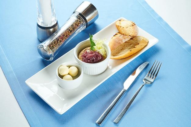 Eine ideale vorspeise - hühnerleberpastete mit karamellisierten zwiebeln und roggenbrot in einem weißen teller auf einem weißen tisch