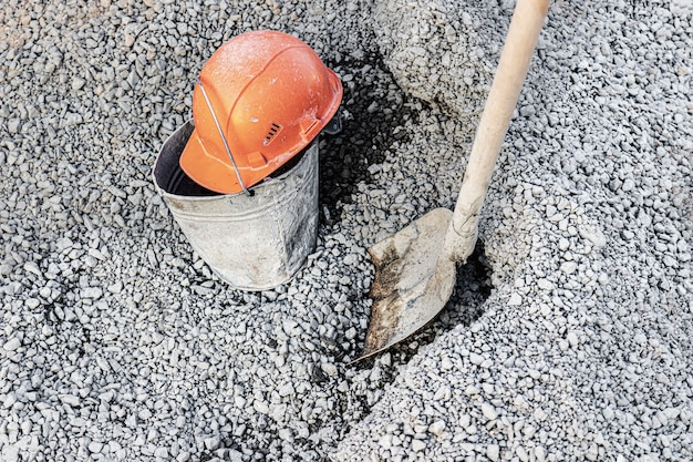 Eine in beton verschmierte schaufel in einem schutthaufen zur vorbereitung von beton und ein orangefarbener bauhelm eines arbeiters liegt auf einem eimer.