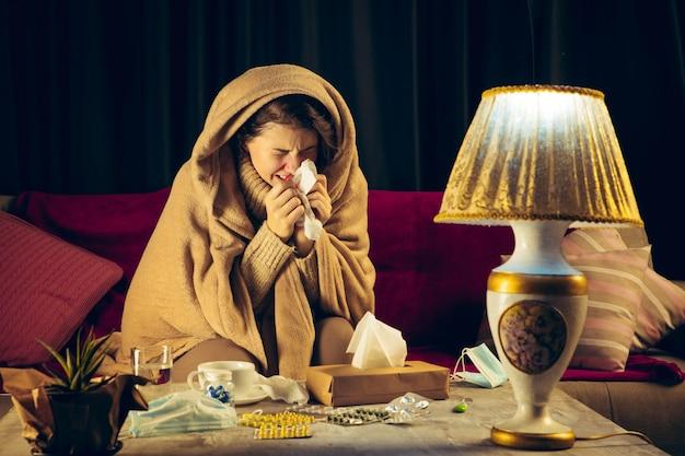 Eine in ein plaid gehüllte frau sieht krank, krank, niesend und hustend aus, wenn sie drinnen zu hause sitzt