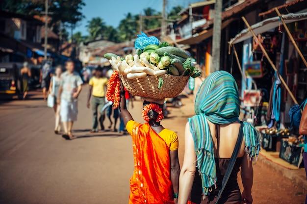 Eine inderin in rotem sari trägt einen großen gemüsekorb auf dem kopf. touristen und einheimische in indien. eine überfüllte straße in gokarna, karnataka