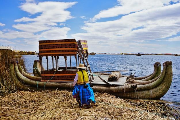 Eine indigene frau begibt sich zu ihrem totora-boot auf eine der schwimmenden uros-inseln auf dem titicaca-see in der nähe von puno, peru.