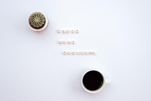 Eine inschrift hegt ihr geschäft auf dem weißen schreibtisch neben einem kaktus und einer tasse kaffee