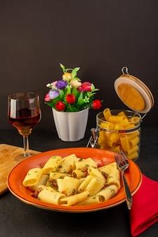 Eine italienische pasta der vorderansicht kochte lecker gesalzenes in runden orangefarbenen teller mit blumen im inneren dip auf entworfenem teppich und dunklem schreibtisch