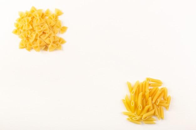 Eine italienische trockene pasta der vorderansicht rohe gelbe pastasammlung, die auf dem weißen hintergrundnahrungsmittelmahlzeititalien gezeichnet wird