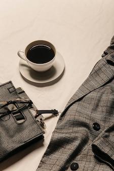 Eine jacke kaffee und eine tasche auf dem bett stilvolles bild