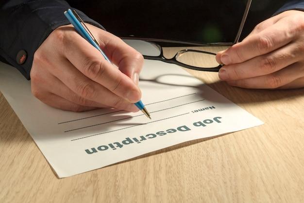 Eine jobbeschreibungsvorlage zum ausfüllen mit stift und händen
