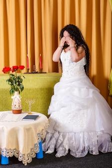 Eine jüdische braut in einem hochzeitskleid mit einem schleier steht im flur und weint, dass ihr bräutigam sie vor der chupa-zeremonie verlassen hat