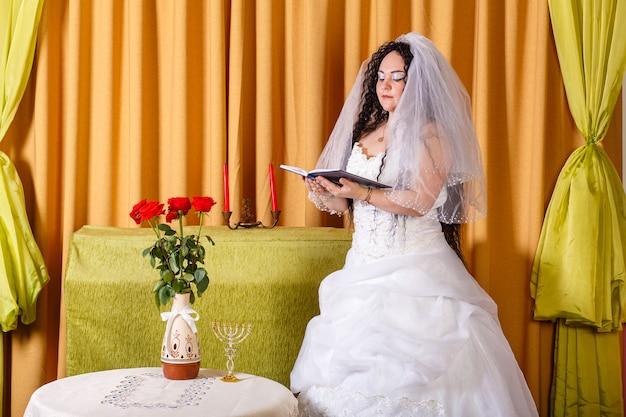 Eine jüdische braut in einem weißen hochzeitskleid mit einem schleier steht in der halle an einem tisch mit blumen und betet vor der chuppa-zeremonie