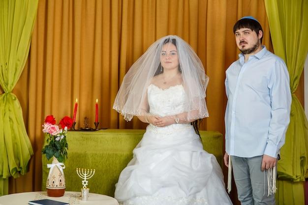 Eine jüdische braut mit einem verschleierten gesicht der badeken-tradition und einem bräutigam in einer synagoge steht während einer zeremonie vor chupa. horizontales foto