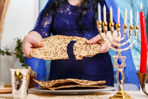 Eine jüdische frau am pessach-seder-tisch bricht die shmura-matze. horizontales foto