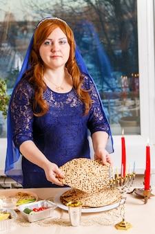 Eine jüdische frau, deren kopf am passah-seder-tisch mit einem blauen umhang bedeckt ist, bricht die matzoh-shmura