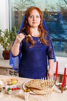 Eine jüdische frau, deren kopf mit einem blauen umhang am pessach-seder-tisch bedeckt ist, erfüllt das gebot karpas