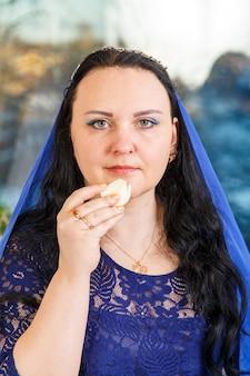 Eine jüdische frau, deren kopf mit einem blauen umhang am pessach-seder-tisch bedeckt ist, führt das gebot karpas mit einem bogen aus. vertikales foto