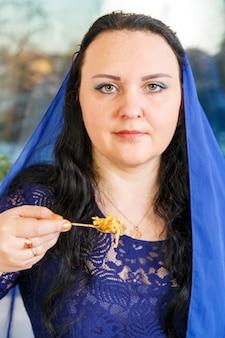 Eine jüdische frau, deren kopf mit einem blauen umhang bedeckt ist, isst am pessach-seder-tisch haroset